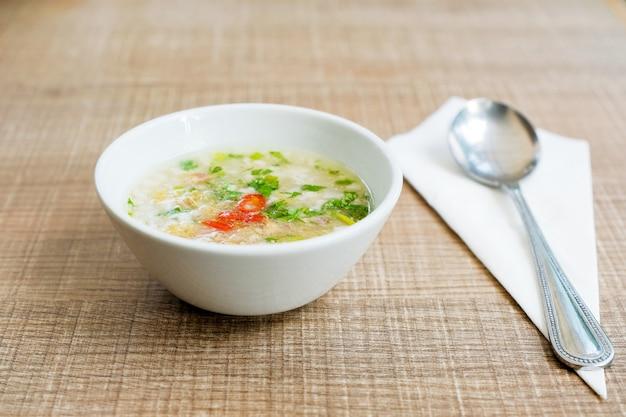 Вареный рис с фаршем из свинины в белой керамической миске на деревянный стол на завтрак.