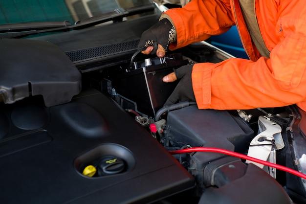 技術者は車の新しいバッテリーを交換しています。