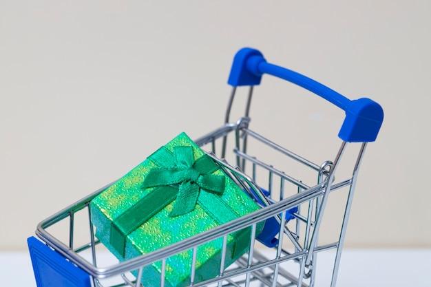 小さなショッピングカートの小さな緑のギフトボックス
