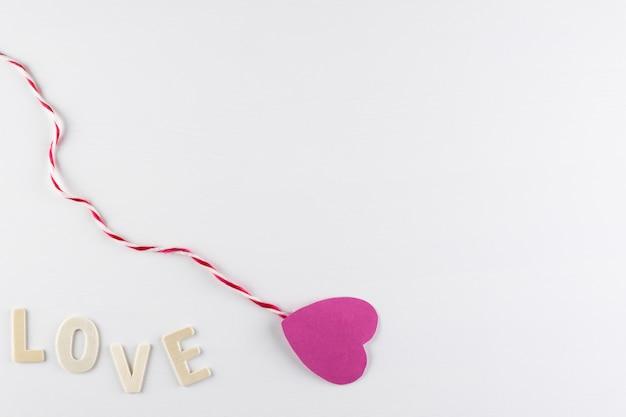 テキスト、愛のアイコン、バレンタインデーのためのスペースと白い背景の上の単語の愛とピンクの心