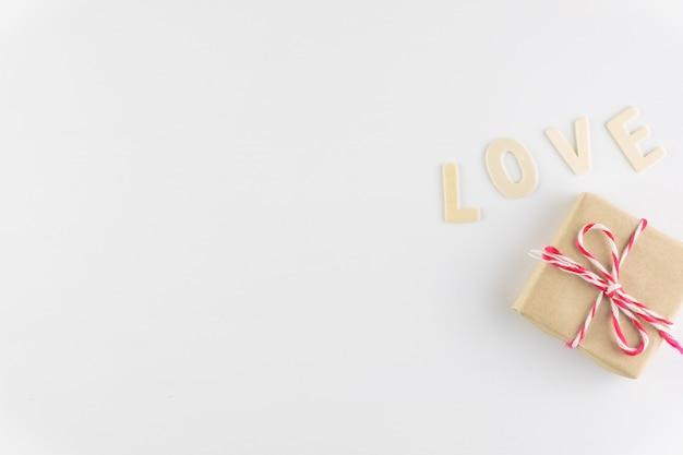 ギフト用の箱とテキスト、バレンタインデーのためのスペースと白い背景の上の愛という言葉