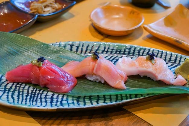 Свежий нарезанный сырой тунец или оторо, чуторо и суши аками сасими, подается с маринованным васаби. японская традиционная еда. выборочный фокус.