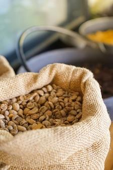 木製のテーブルに置かれた袋に生または未焙煎のコーヒー豆