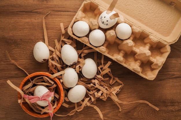 イースター、木製ボウルに赤いリボンで結ばれた卵、木製テーブルの卵トレイにウサギの顔のような卵を描いた