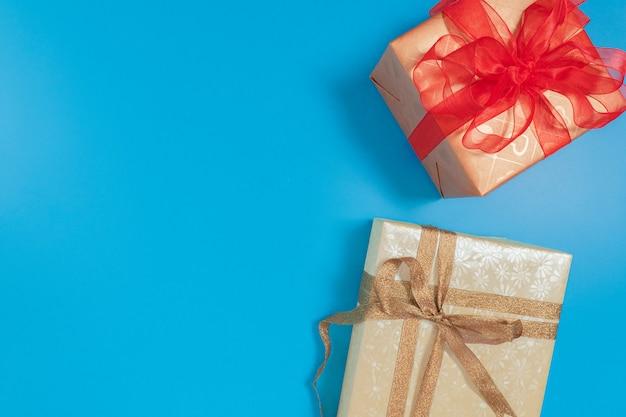Подарочная коробка, перевязанная блестящей коричневой лентой, и коричневая подарочная коробка, перевязанная полупрозрачной красной лентой, надетой на синий