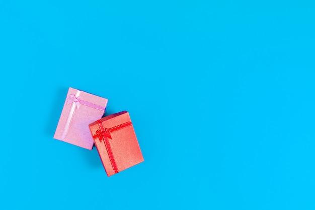 青色の背景に結ばれたピンクのギフトボックスに縛ら赤いギフトボックス