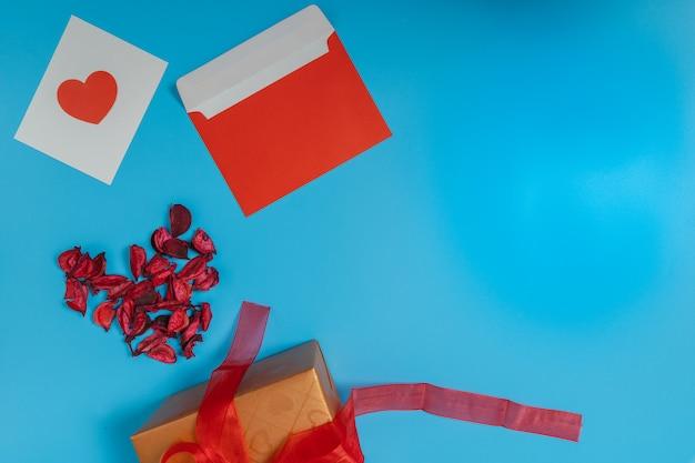 Красное сердце на белой бумаге, красный конверт, высушенный красный лист и коричневая подарочная коробка, перевязанная красной лентой.