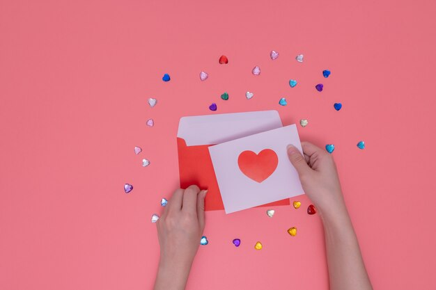 赤い封筒と白い紙に赤いハートを保持している右手。