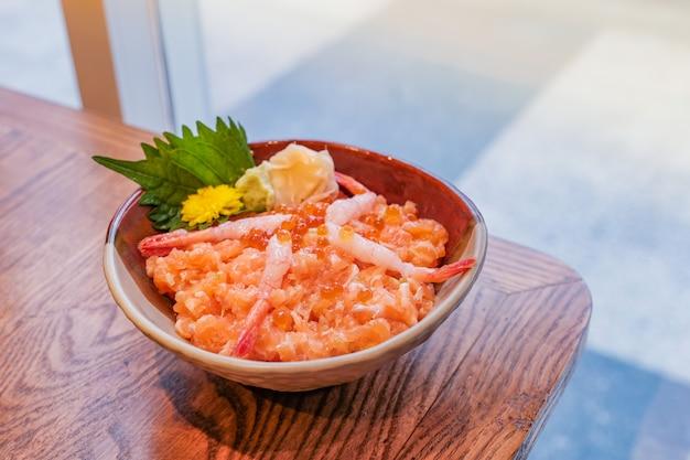 日本食、木製のテーブルに置かれたサーモンとエビのミンチのボウル