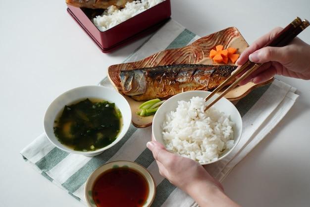 Кто-то держит в руках миску с вареным рисом и использует палочки для еды, пытаясь собрать рис, подаваемый с жареной сабой или скумбрией и супом мисо на белом и зеленом полосатом столовом приборе на белом столе