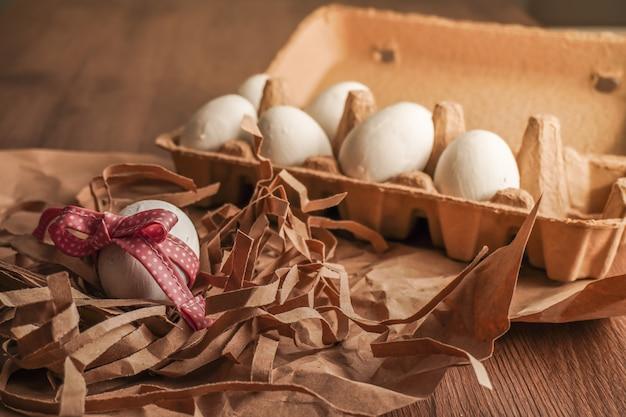 Пасха, связанное яйцо с красной лентой и белые яйца на коричневой бумаге и на подносе для яиц на деревянном столе