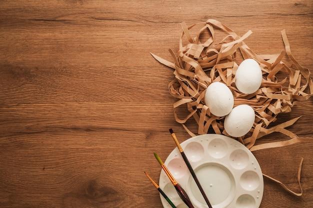 イースター、茶色の紙の白い卵、絵筆、木製のテーブルの色皿