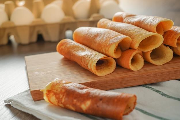 木製のテーブルと卵の背景のパックに白と緑の縞模様の布に置かれた竹のまな板に盛り合わせパンケーキロール各種フレーバー