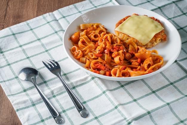 パスタ、イタリア料理、トマトソースのトッピングのカリカリポークカツとチーズのシートを白い皿に布とダークブラウンの木製テーブルの上に配置