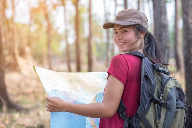 地図で森の中を歩く美しい女性。
