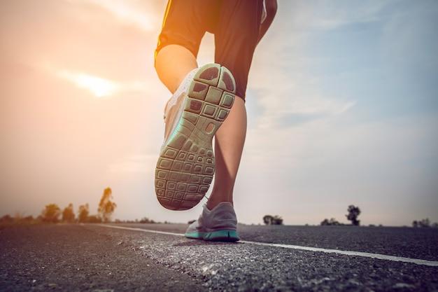 太陽と道路をジョギングする男。