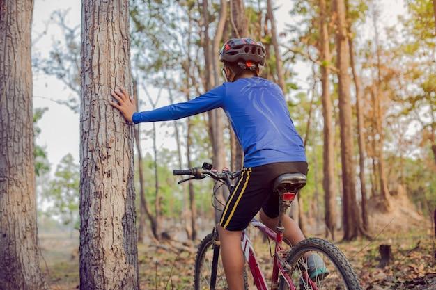 森の中でマウンテンバイクに乗っている子供。