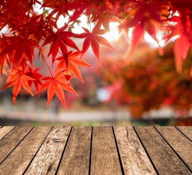 廊下の庭でぼやけている赤いカエデの葉の上の木製のテーブルトップ