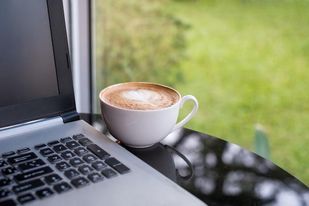 机の上の白いカップにラテホットコーヒーとノートパソコン