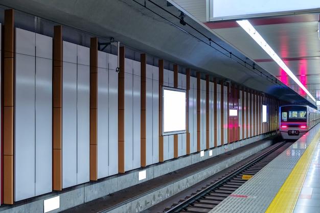 壁にビルボードとプラットフォームの駅を走る列車
