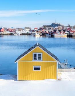 漁村の雪の上の黄色い家