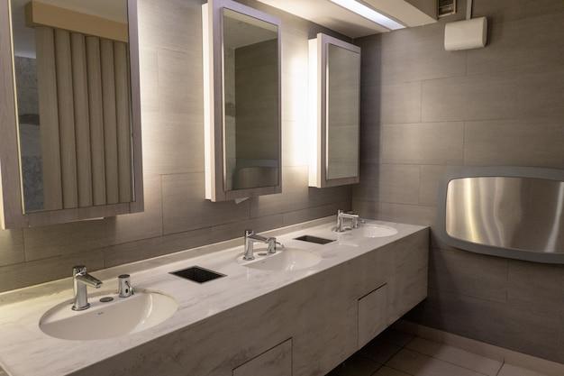 公衆トイレの鏡の中の光で豪華な大理石の洗面器
