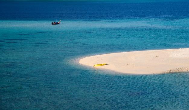 熱帯の海で黄色いカヌーと白いビーチ