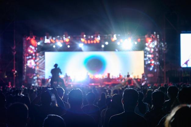 シルエットの若者の観客が夜のコンサートを見ています