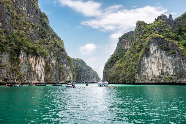 ピレラグーン石灰岩の山に囲まれ、クラビで旅行する観光客とエメラルドの海