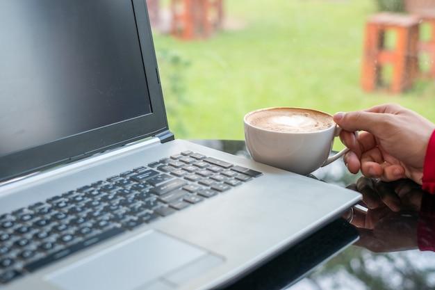 Вскользь человек держа кофейную чашку с компьтер-книжкой в офисе