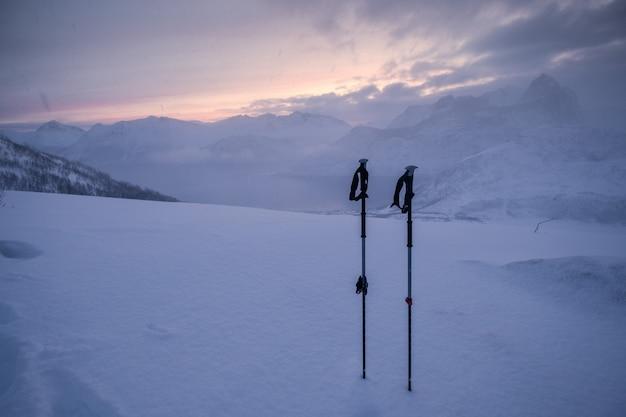 吹雪の雪に覆われた丘の上の登山者のトレッキングポール