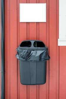 木製の壁に掛かっている袋を持つプラスチック製のゴミ