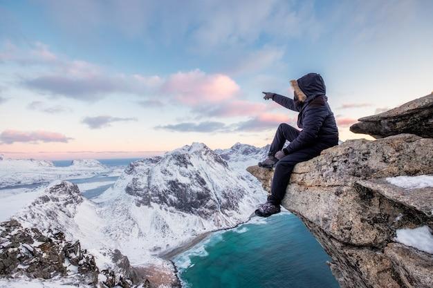 登山家の夕暮れ時の北極の海岸線のピーク山で岩の上に座って