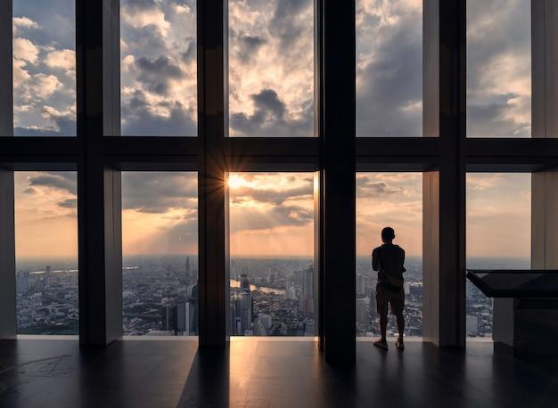 Человек стоит и осматривает город бангкок через окна