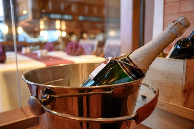 Бутылка шампанского замачивается в ведре