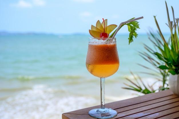 熱帯の海でワイングラスにチェリーとアップルのカクテル