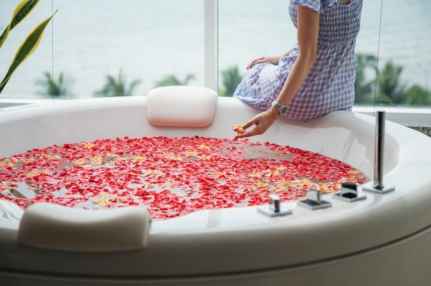 Молодая женщина расслабляющий на роскошной ванной с розами листьев