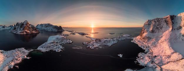 日の出の海岸線に山と北欧の群島のパノラマ空撮