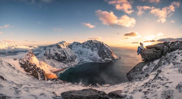 夕暮れ時の北極の海岸線のピーク山の上の岩の上に座っての登山家のパノラマ