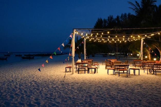 ダイニングテーブルは、ビーチに輝くランプと色のフラグで装飾を設定します