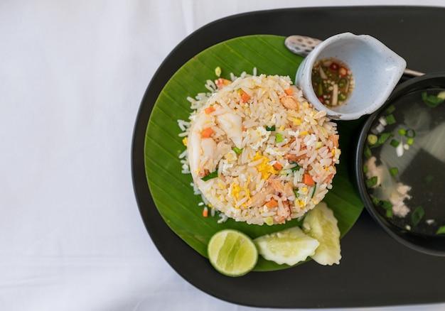 Крабовое мясо жареный рис тайской кухни с жареным яйцом, овощами и супом