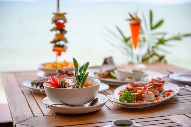 Разнообразные блюда, жареные свиные ребрышки, стейк из говядины, морепродукты и острый суп на обеденном столе