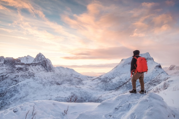 観光客の男が雪に覆われた山の上に登る