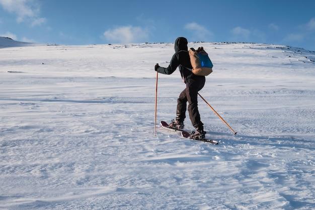 雪の丘に登るトレッキングポールを持つ男スキーヤー