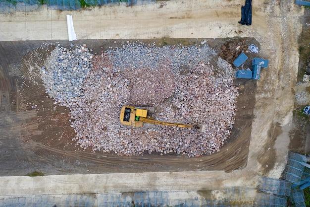 建設現場でのヒープ岩の黄色のバックホウローダー
