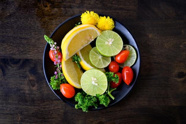 ボウルにレモン、ライム、トマト、パセリのさまざまな果物