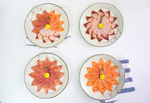 Нарезанный сырой лосось, хамачи, сагуми магуро на керамическом блюде