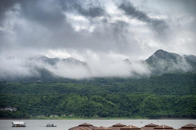 霧と雨季のダムでセーリングボートと山の風景