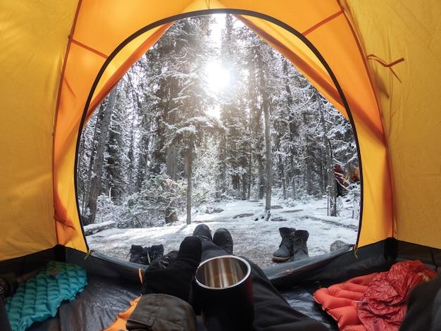 松の森で雪と黄色いテントでカップを持っている手でキャンプ