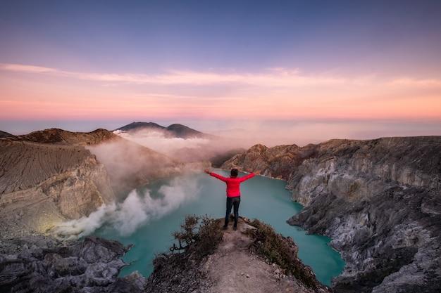 Женщина, стоящая на хребте в действующем вулкане с дымом серы утром